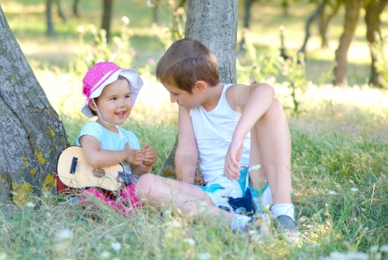 Boy and his younger sister play guitar and sing in garden