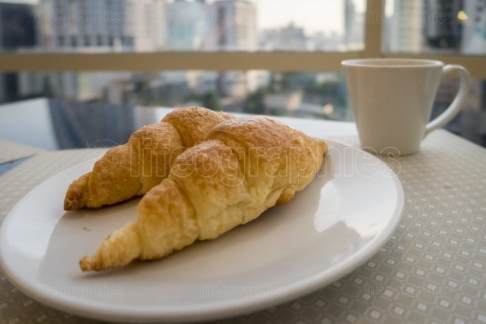 Breakfast with coffee and fresh croissants, selective focus