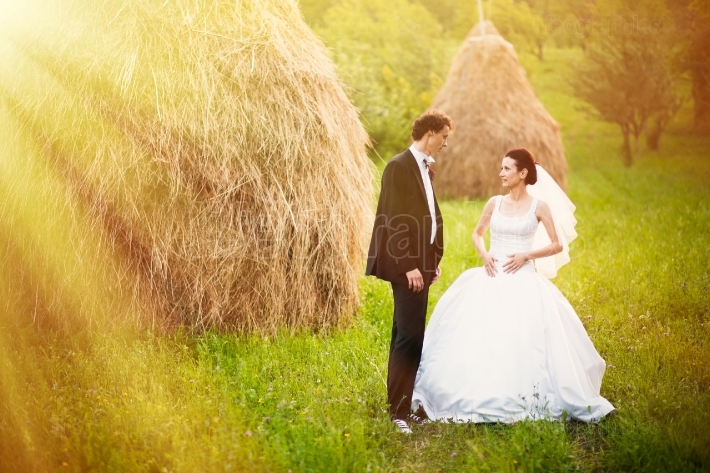 Bride and groom in the hay field