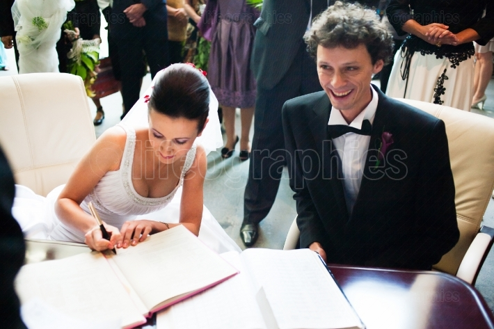 Bride and groom signing registry