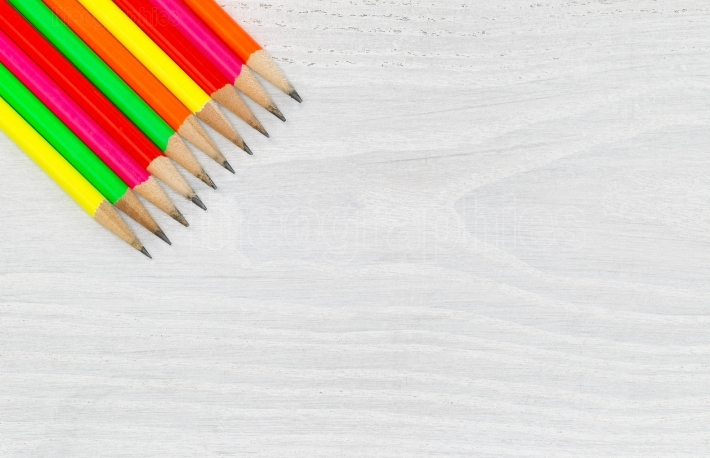 Bright colorful pencil tips on white wood desktop