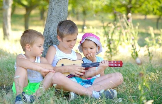 Brothers play guitar and sing in garden