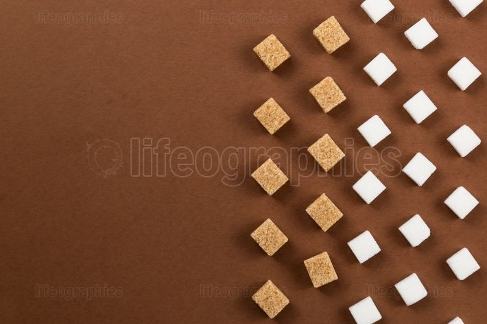Brown and white sugar cubes on brown background