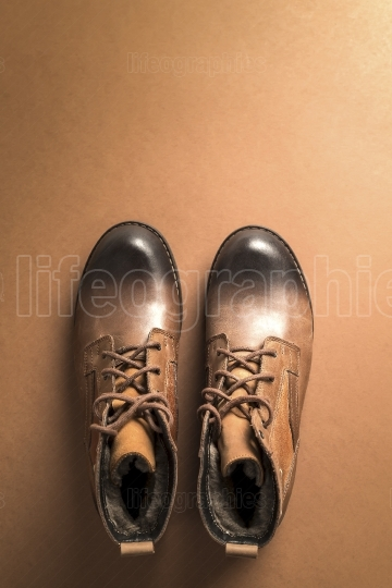 Brown leather boots over brown background,above view with copy s