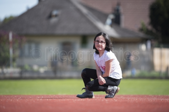 Brunette girl posing on a sports facility