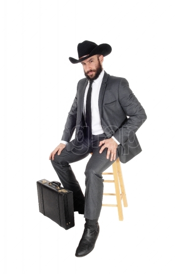 Business man sitting with hat and briefcase