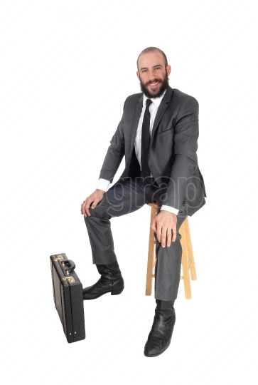 Business man sitting with his and briefcase