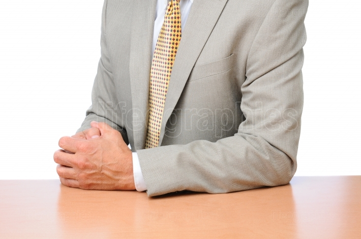 Businessman Seated at Desk Hands Folded