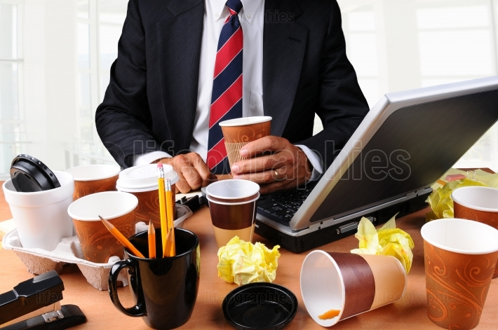 Businessman Seated at His Messy Desk