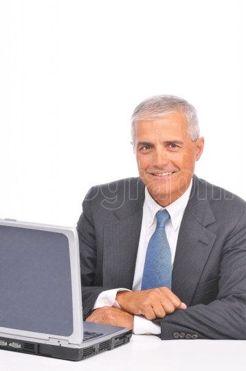 Businessman seated looking over top of laptop