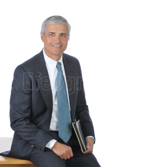 Businessman seated on the edge of his desk