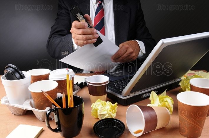 Businessman Stapling Papers at Messy Desk