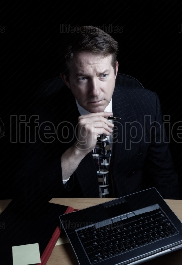 Businessman with serious look checking data late at night