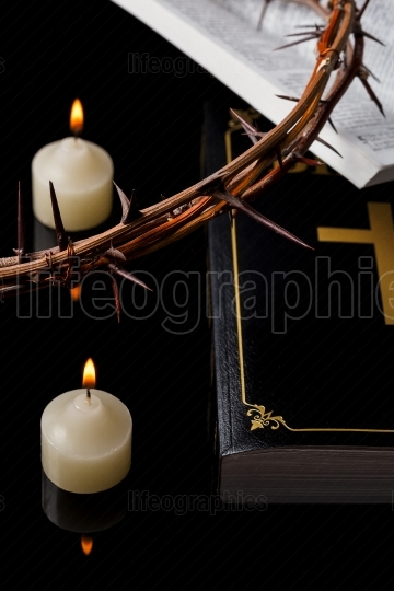 Candles with crown of thorns and Holy Scripture on black backgro