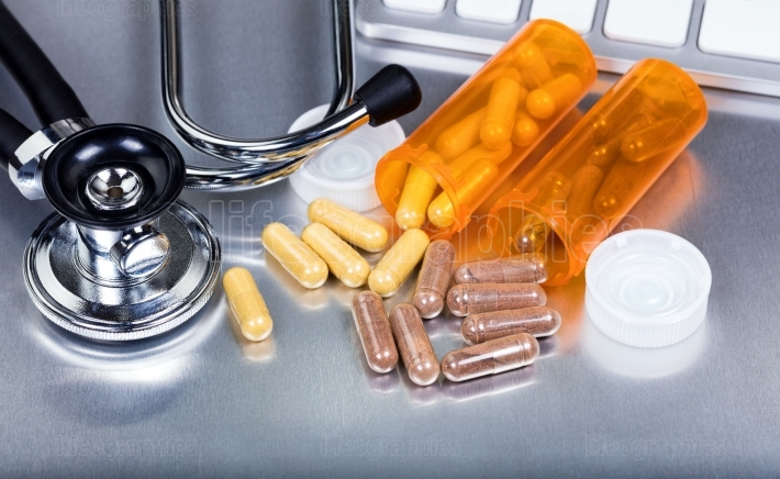 Capsules and medicine bottles plus medical equipment on stainles