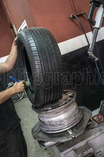 Car mechanic hands lubricating tire before mounting the rim