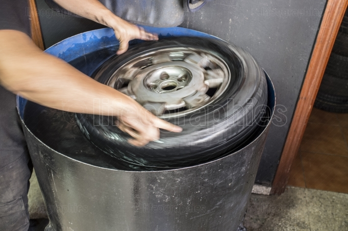 Car mechanic hands sink on water tank the tyre