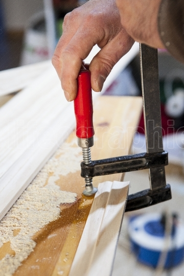 Carpenter fastening a clamp