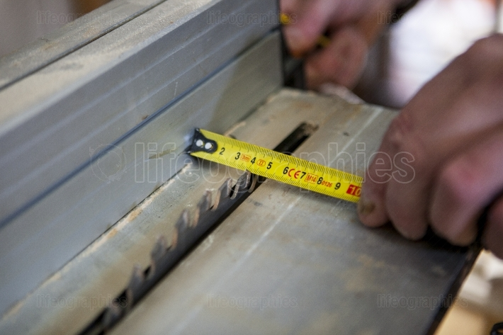 Carpenter measuring the cutting area of circular saw