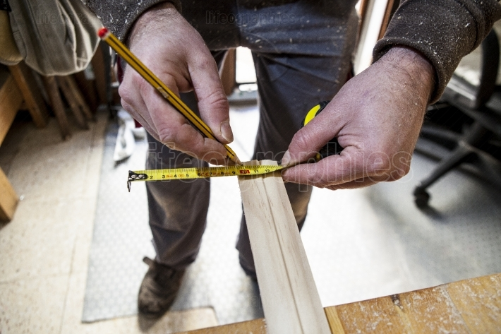 Carpenter measuring wood and marking with pencil