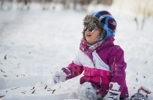 Caucasian little girl in winter clothes playing in the snow