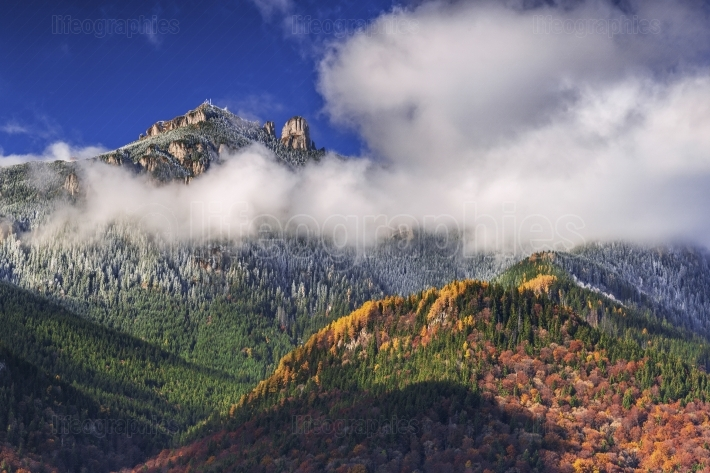 Ceahlau Peak in fog with rusty forest in the middle of autumn se