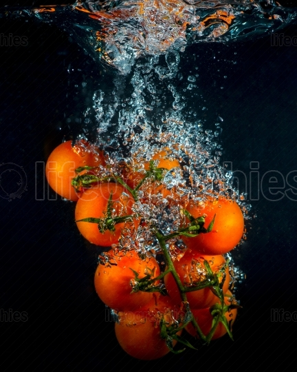 Cherry tomatoes in water splash on black background
