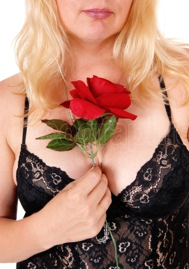 Chest of woman in lingerie and rose.
