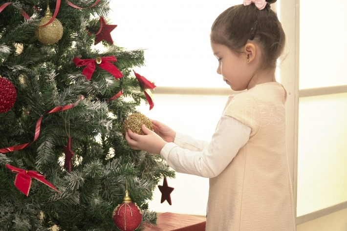 Child decorating Xmas tree in family living room
