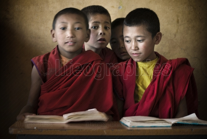 Child monks seated at the table in front of study books