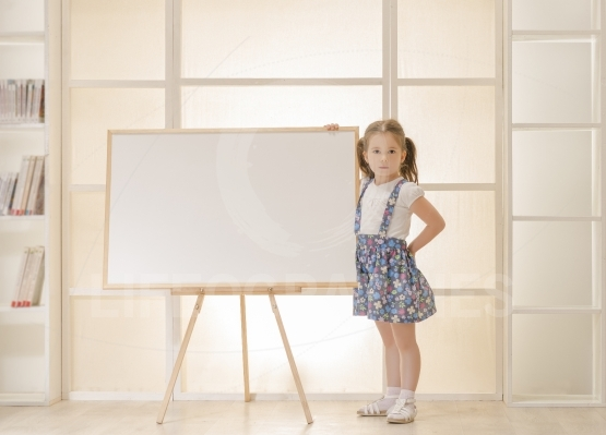 Child standing next to blank clipboard