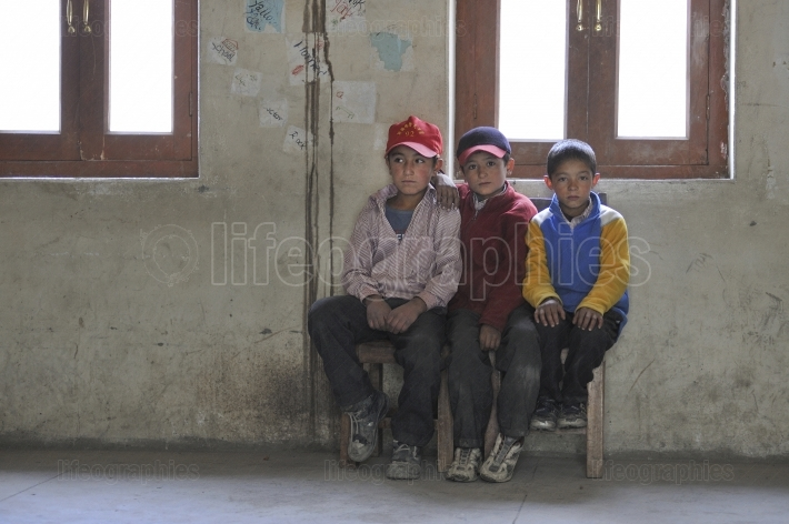 Children sit on government school bench
