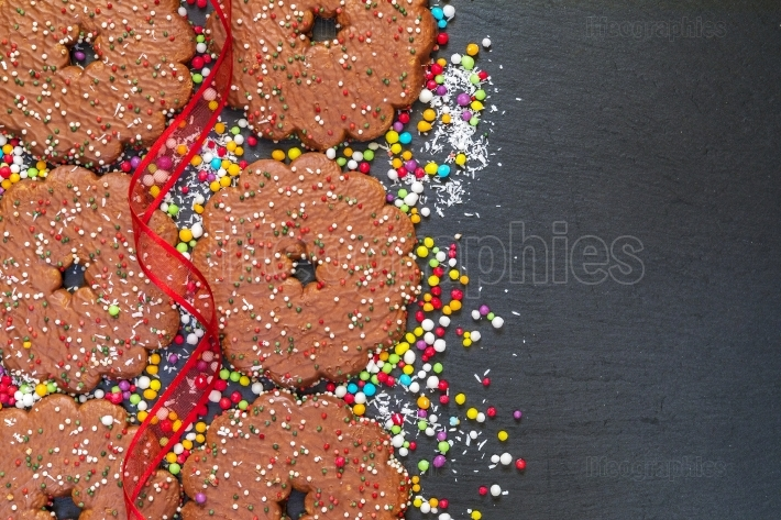 Chocolate biscuits rings with Christmas decoration on black slat