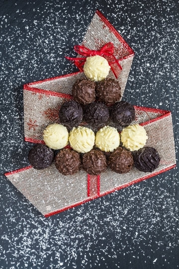 Chocolate pralines shape Christmas tree on black