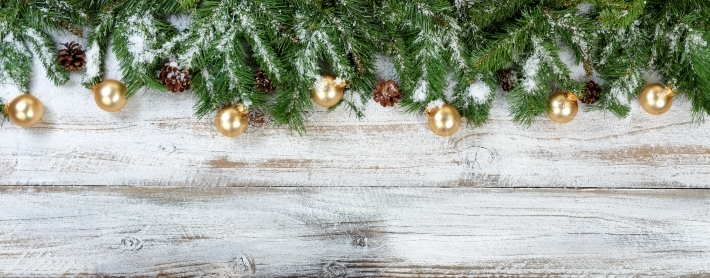Christmas branches and golden ornaments with snow on rustic whit