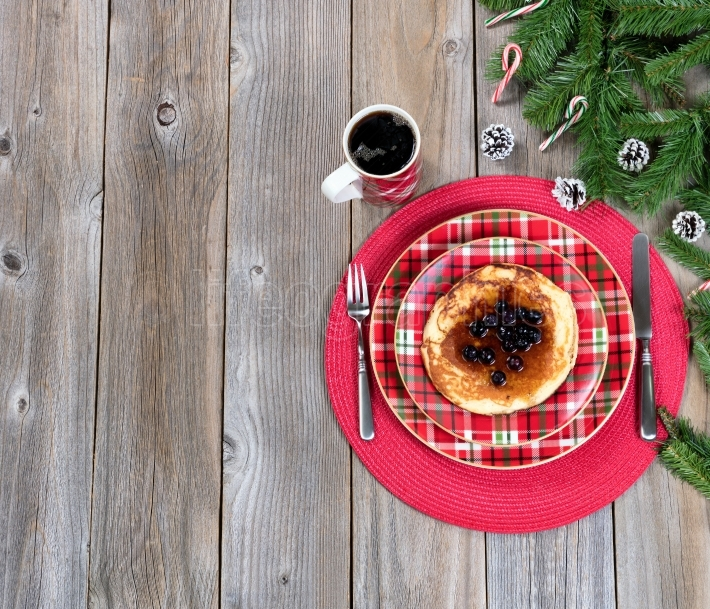 Christmas breakfast setting with evergreen branches on rustic wo
