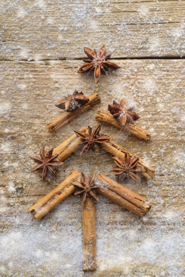 Christmas card with Christmas fir tree made from spices cinnamon sticks, anise star and cane sugar