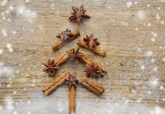Christmas card with Christmas fir tree made from spices cinnamon sticks, anise star and cane sugar on rustic wooden background