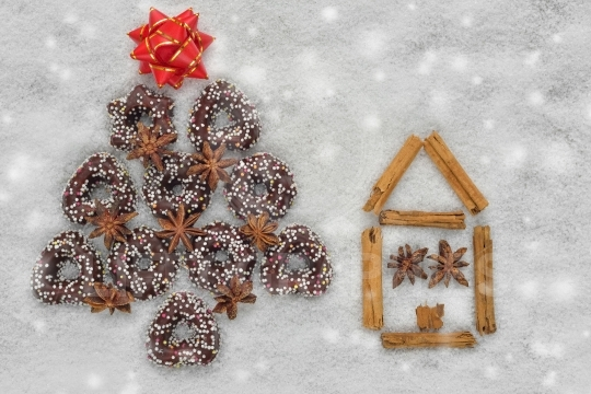 Christmas cookies tree near a house made by cinnamon with snowy background