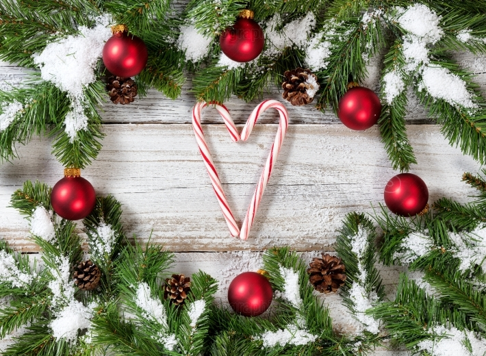 Christmas snowy tree branches with candy canes forming heart