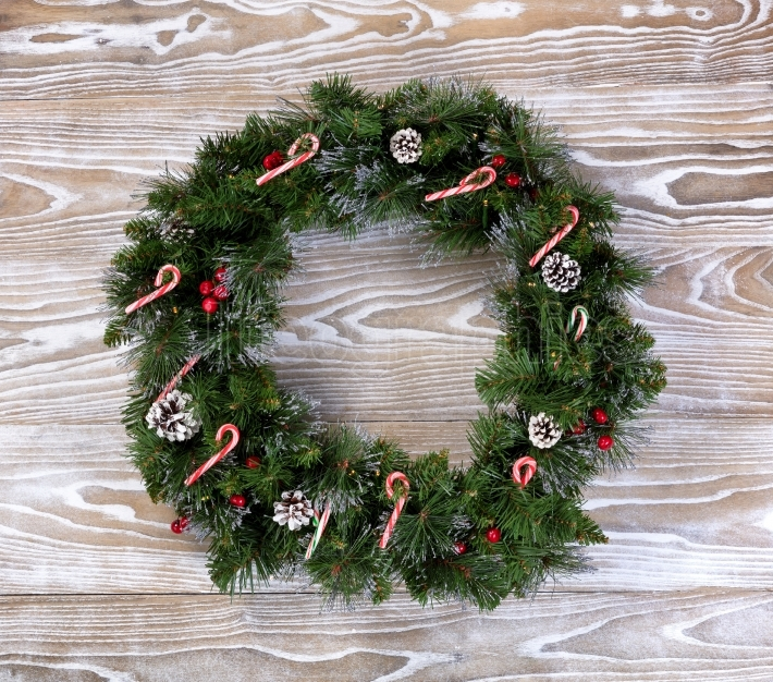 Christmas wreath with lights and candy canes on white wooden boa