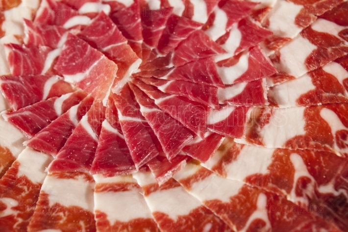Circular decorative arrangement of iberian cured ham on plate