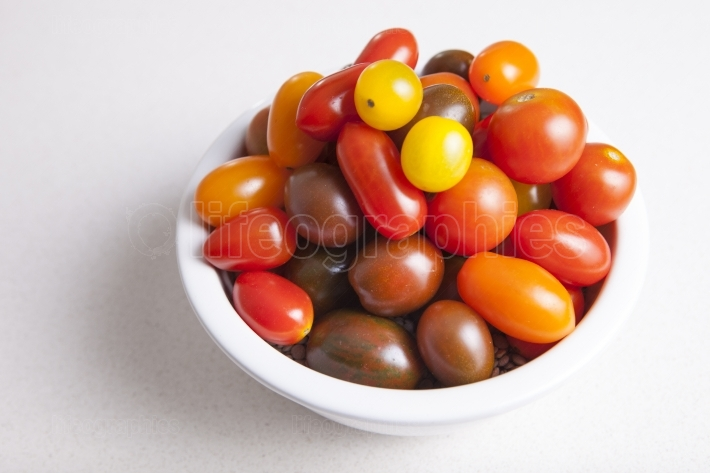 Clay bowl full of several varieties of cherry tomatoes