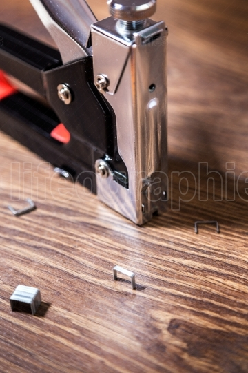 Close up carpentry stapler with staples on wood background