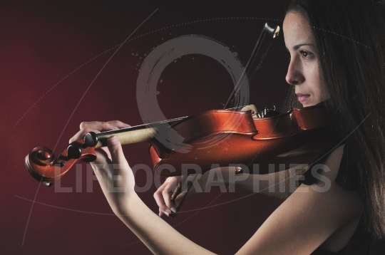 Close up of a pretty young woman playing a violin