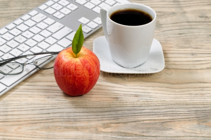 Close up of a ripe red apple for office snack on wooden desktop