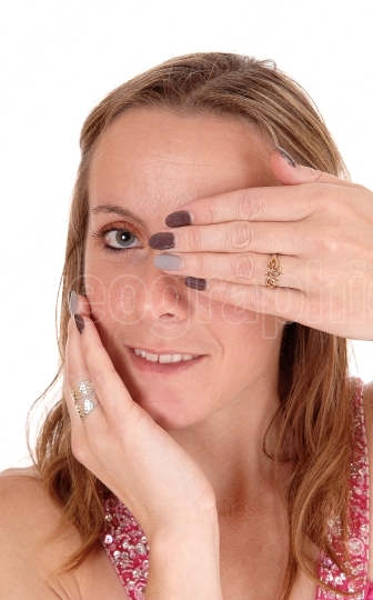 Close up of face of woman holding hand over eye
