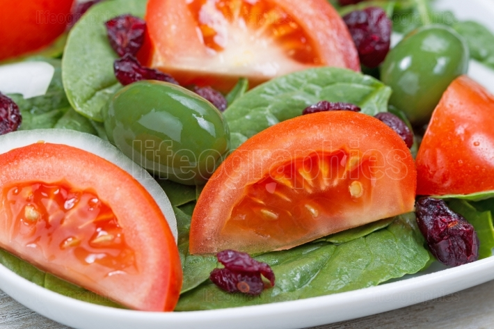 Close up of Fresh Spinach Salad on White Plate