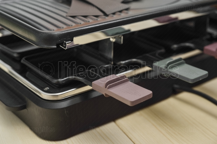 Close up of handle trays of a raclette machine