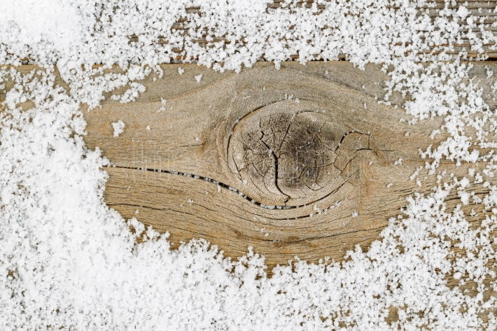 Close up of snow on rustic wood